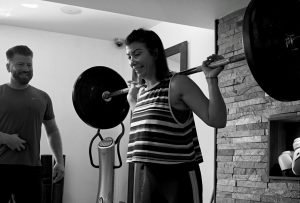 personal trainer instructing female lifting heavy weights